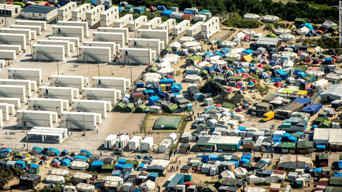 "This aerial view taken Tuesday, August 16, shows the tents and shipping containers housing migrants in ""The Jungle."""