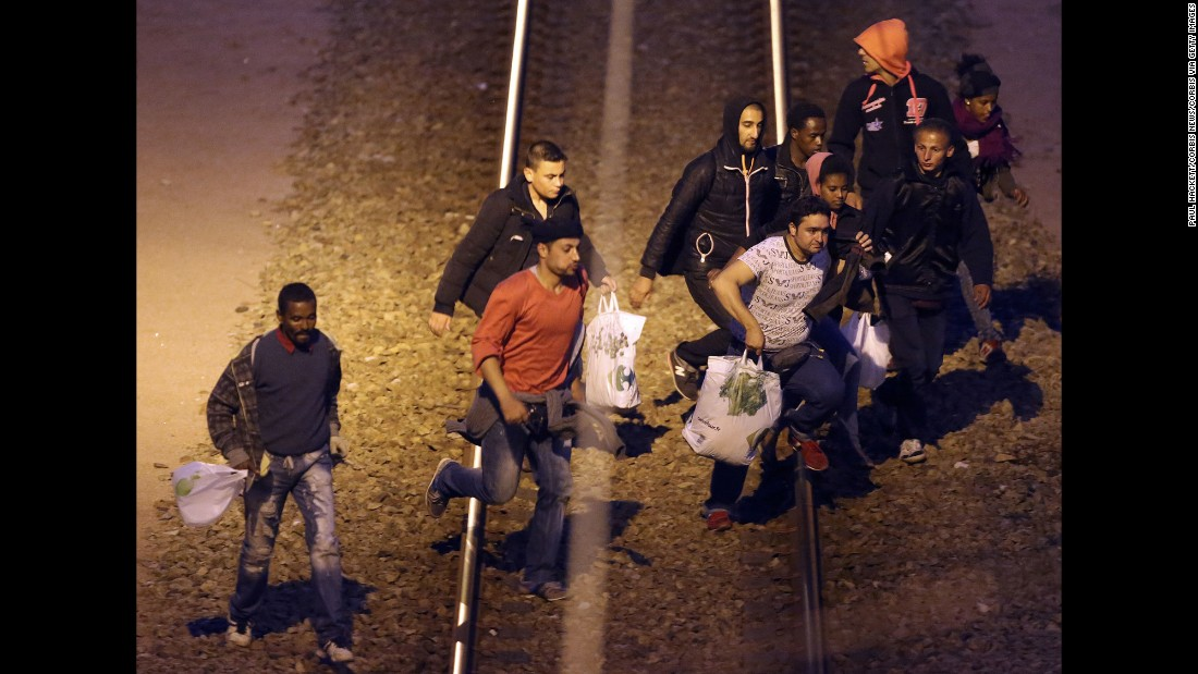 Migrants walk along the railway track leading to the Eurotunnel in Calais in August 2015. Migrants attempt to enter the UK illegally by stowing away on trucks, ferries, cars or trains.