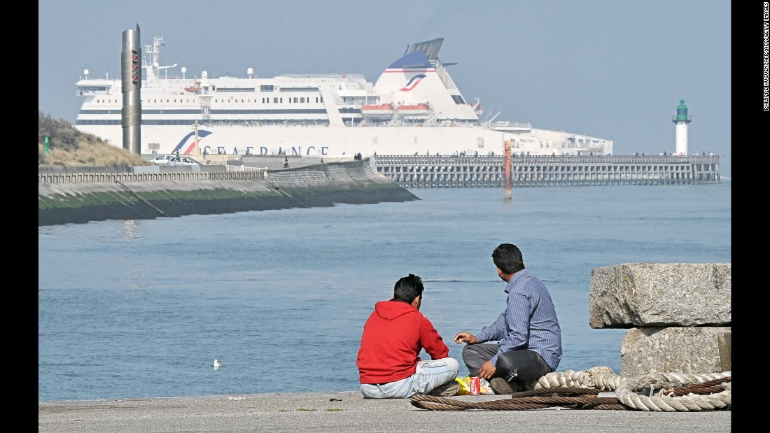 Migrants from Afghanistan look at a ferry boat in Calais in September 2009.