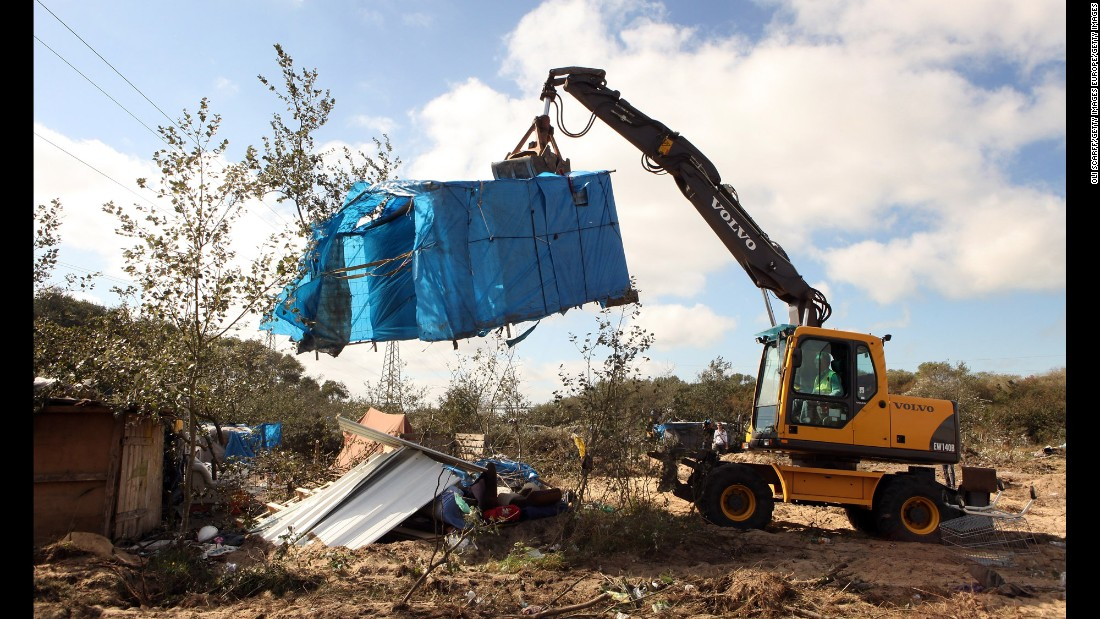 A digger lifts a migrant's makeshift tent during a destruction operation in September 2009.