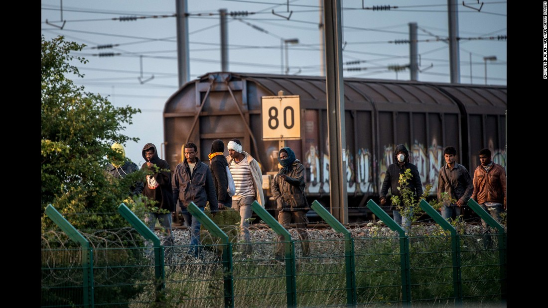 Several migrants successfully cross the Eurotunnel terminal in July 2015 as they try to reach a shuttle to the UK.