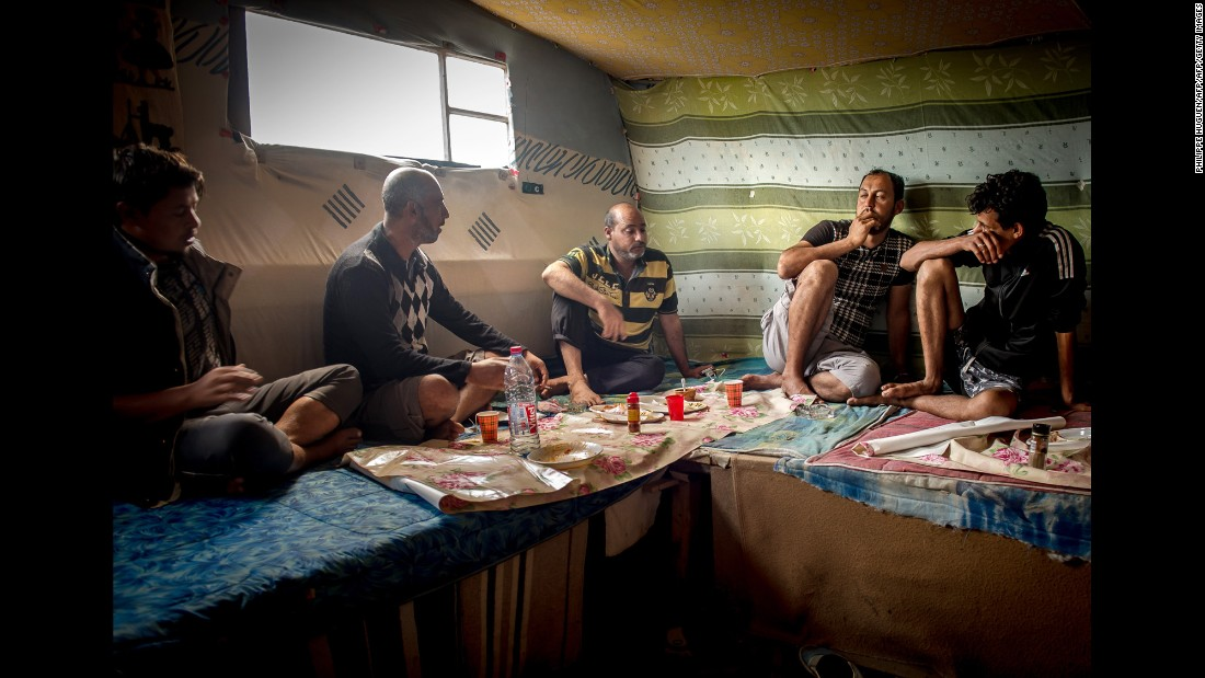Afghan and Pakistani migrants eat lunch in the migrant camp in August 2015.