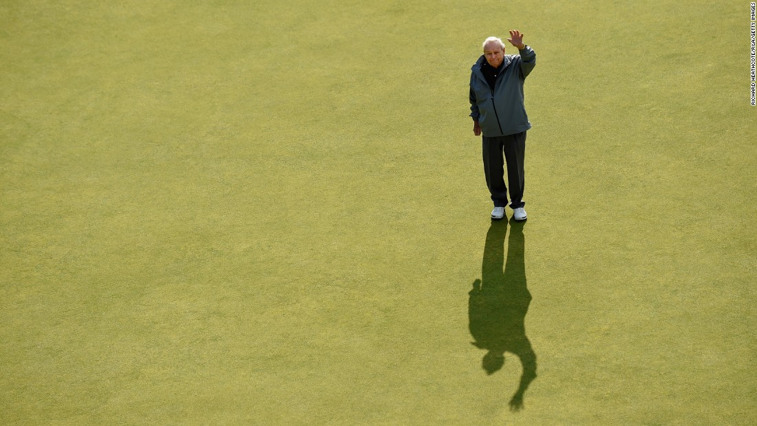 Palmer waves on the eighteenth green during the Champion Golfers' Challenge ahead of the 2015 British Open.