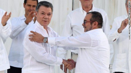 "Colombian President Juan Manuel Santos (L at centre) and the head of the FARC guerrilla Timoleon Jimenez, aka Timochenko, shake hands during the signing of the historic peace agreement between the Colombian government and the Revolutionary Armed Forces of Colombia (FARC), in Cartagena, Colombia, on September 26, 2016  Colombia will turn the page on a half-century conflict that has stained its modern history with blood when the FARC rebels and the government sign a peace deal on Monday. President Juan Manuel Santos and the leader of the FARC, Rodrigo Londono -- better known by his nom de guerre, Timoleon ""Timochenko"" Jimenez -- are set to sign the accord at 2200 GMT in a ceremony in the colorful colonial city of Cartagena on the Caribbean coast. / AFP / Luis ACOSTA        (Photo credit should read LUIS ACOSTA/AFP/Getty Images)"