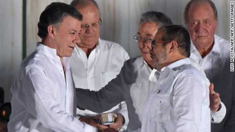 "Cuban President Raul Castro greets Colombian President Juan Manuel Santos (L) and the leader of the FARC, Rodrigo Londono -- better known by his nom de guerre, Timoleon ""Timochenko"" Jimenez after the latter delivered a speech after signing the historic peace agreement between the Colombian government and the Revolutionary Armed Forces of Colombia (FARC), in Cartagena, Colombia, on September 26, 2016  The Colombian government and the leftist FARC rebel force signed a historic peace accord to end a half-century conflict that has killed hundreds of thousands of people. Santos and ""Timochenko"" Jimenez, signed the deal at a ceremony in the Caribbean city of Cartagena, prompting loud cheers from the crowd which included numerous international dignitaries.  / AFP / Luis ACOSTA        (Photo credit should read LUIS ACOSTA/AFP/Getty Images)"