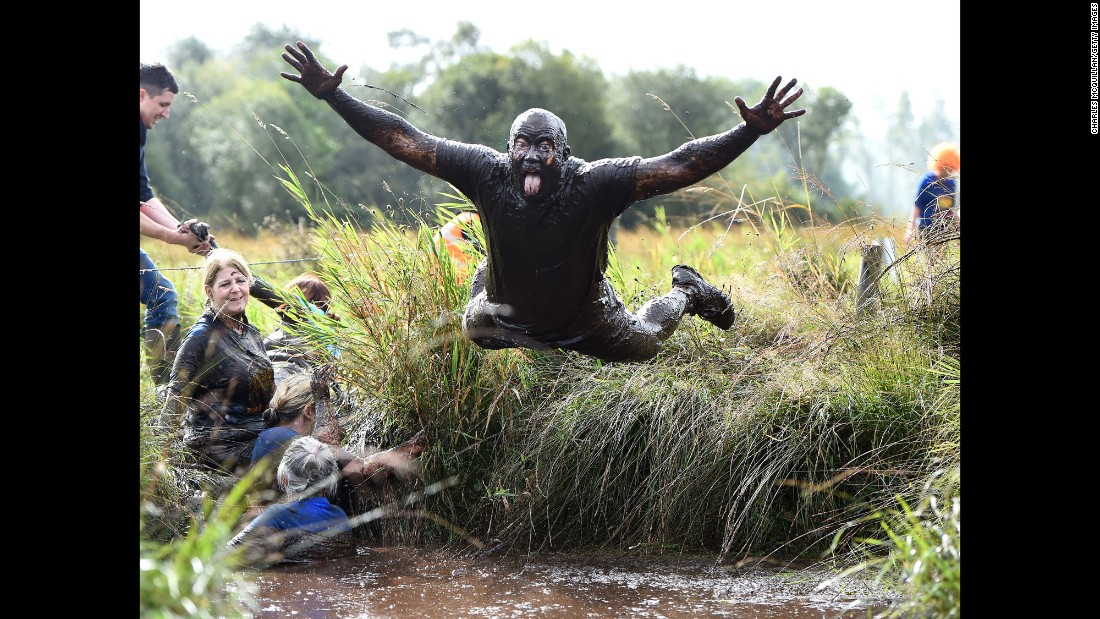 "A man dives into the mud Sunday, September 25, during a charity ""Mud Madness"" race in Portadown, Northern Ireland."