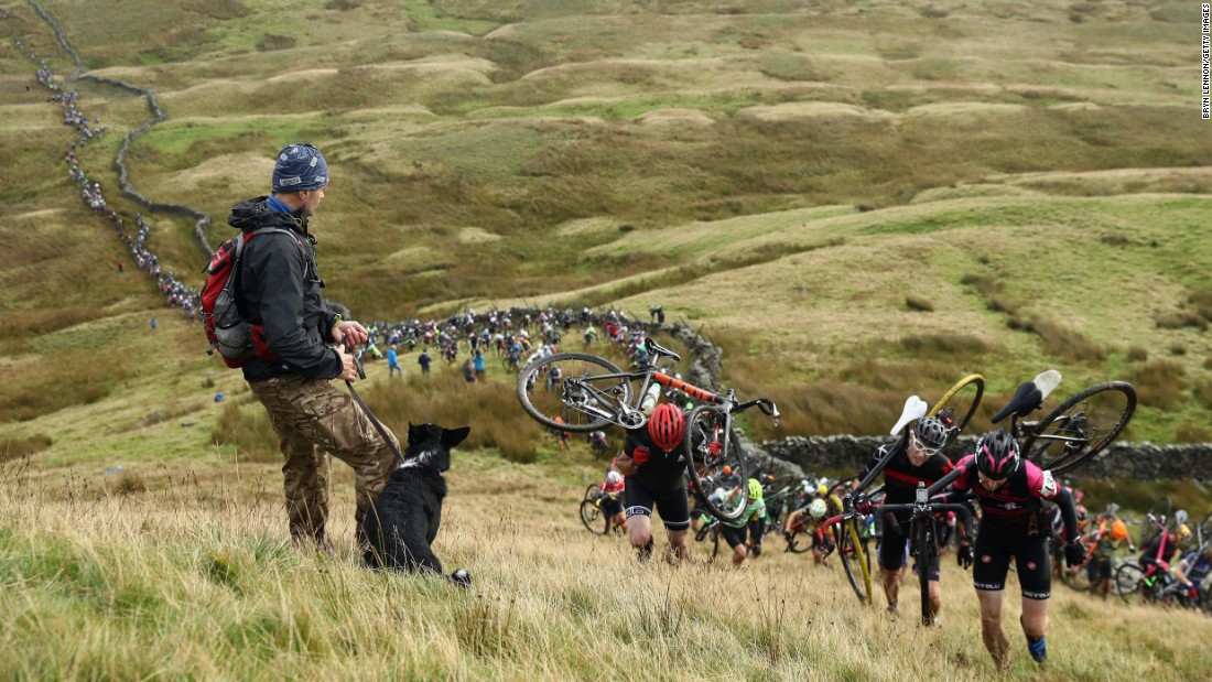 "A man and his dog watch riders climb Simon Fell at the start of the Three Peaks Cyclo-Cross race in Helwith Bridge, England, on Sunday, September 25. <a href=""http://www.cnn.com/2016/09/19/sport/gallery/what-a-shot-sports-0920/index.html"" target=""_blank"">See 28 amazing sports photos from last week</a>"