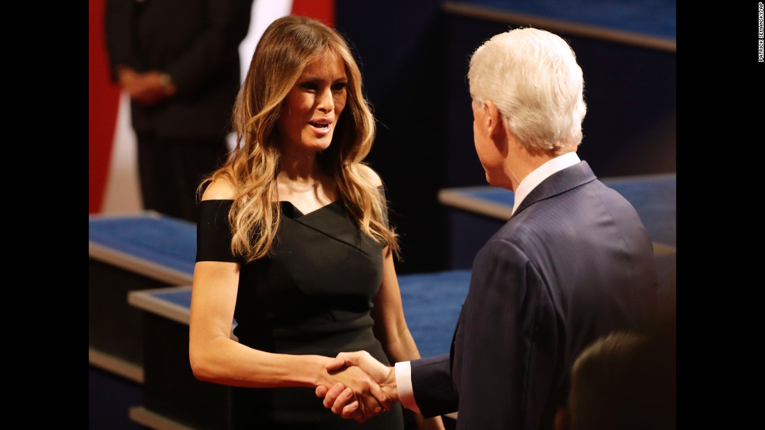 Trump's wife, Melania, shakes hands with Clinton's husband, former U.S. President Bill Clinton.