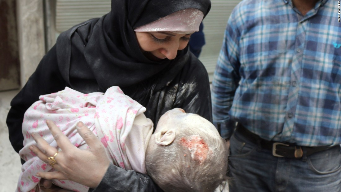 A Syrian woman carries the body of her infant after he was recovered.