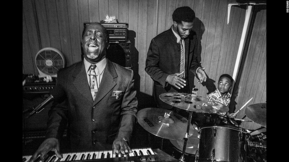 Pastor Roger Foster, the founder of the church, plays a keyboard while Willie helps his young son keep his timing on the drums.