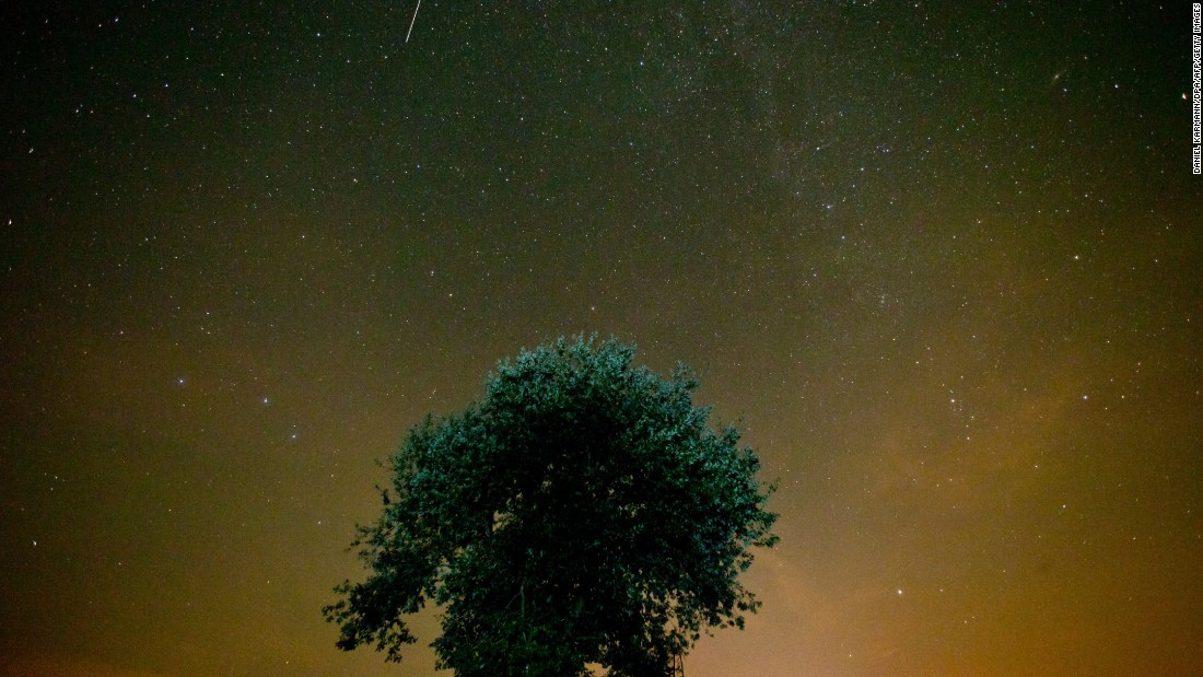 A shooting star crosses the night sky near Muenchsteinach, southern Germany, during the peak in activity of the annual Perseids meteor shower on August 13, 2015.