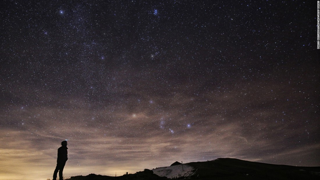 A photographer looks at the sky at night in northern Italy during the 2015 Geminid meteor shower.