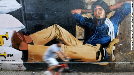 "An Indian cyclist rides past a mural of Bollywood actor Amitabh Bachchan from his classic film ""Deewar"" on the eve of Bachchan's 70th birthday in Mumbai on October 10, 2012."