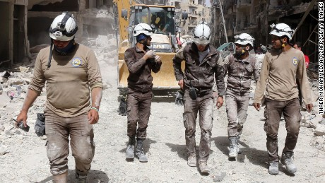 Syrian civil defence volunteers, known as the White Helmets, walk amidst the debris following a reported air strike by Syrian government forces in the rebel-held neighbourhood of Sukkari in the northern city of Aleppo on June 3, 2016. Regime air strikes killed dozens of civilians in the Syrian city of Aleppo and nearby areas as the UN Security Council prepared to discuss emergency aid drops to besieged areas. / AFP / THAER MOHAMMED        (Photo credit should read THAER MOHAMMED/AFP/Getty Images)