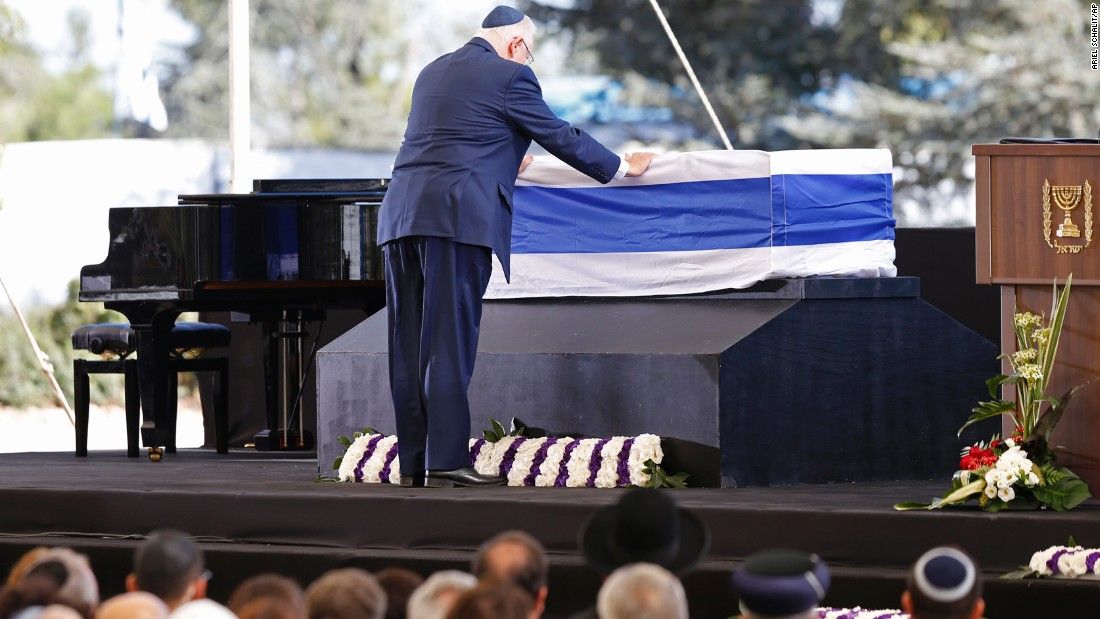 "Israeli President Reuven Rivlin touches Peres' coffin. In his tribute, Rivlin said that Peres was ""the man of whom we thought time could never stop."""