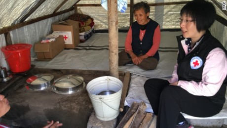 A Red Cross relief worker from the DPRK talks to flood survivors who received Red Cross relief supplies in Musan County.