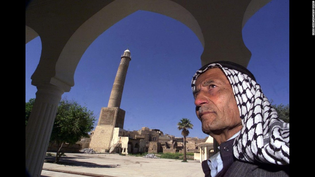 "In this 2001 photo, a man stands before the Great Mosque's minaret, which leans like the Tower of Pisa and is nicknamed ""al-Habda,"" or ""the hunchback."""