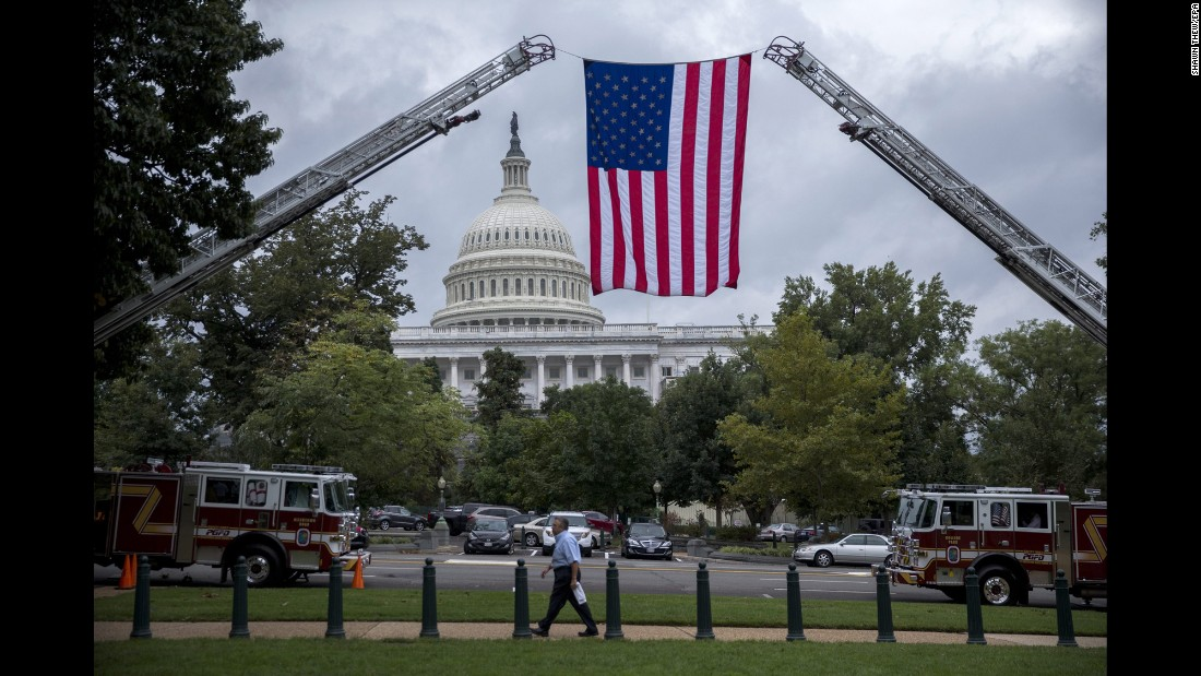 "An American flag is suspended from the ladders of two fire trucks in Washington on Wednesday, September 28. Congress had just voted <a href=""http://money.cnn.com/2016/09/28/news/override-obama-veto-911-bill/"" target=""_blank"">to override a presidential veto</a> on legislation that would allow the families of 9/11 victims to sue the government of Saudi Arabia."