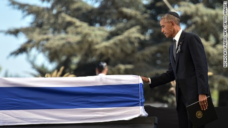 US President Barack Obama touches the flag-draped coffin of former Israeli president and prime minister Shimon Peres after speaking during his funeral at Jerusalem's Mount Herzl national cemetery on September 30, 2016. World leaders bid farewell to Israeli elder statesman and Nobel Peace laureate Shimon Peres at his funeral in Jerusalem, with US President Barack Obama hailing him as a giant of the 20th century. / AFP / NICHOLAS KAMM        (Photo credit should read NICHOLAS KAMM/AFP/Getty Images)