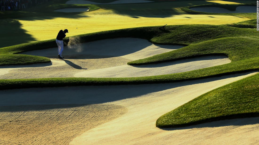 Jimmy Walker of the United States hits out of a bunker on the first hole.