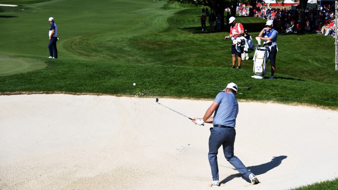 Lee Westwood of Europe hits out of a bunker on the first hole during singles matches. His opponent Ryan Moore later sealed the victory for the US.