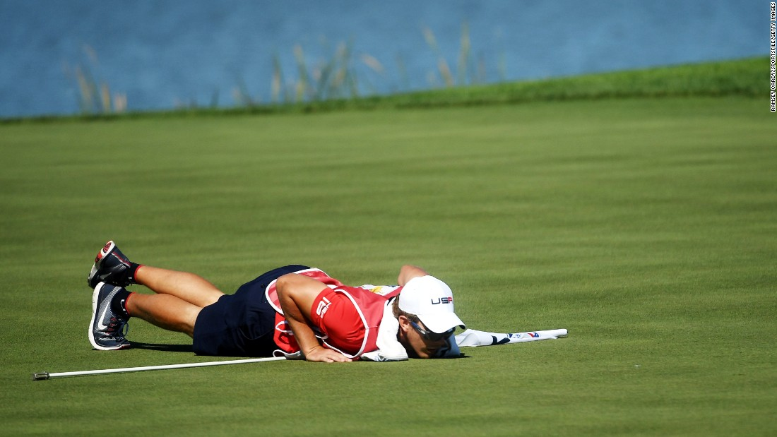 The caddie for Patrick Reed of USA, Kessler Karain, checks the line for a putt on the seventh green.