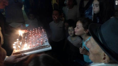 Kristal watches on as younger family members help blow out his candles.