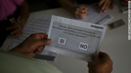 A Colombian citizen receives the ballot before voting in a referendum on whether to ratify a historic peace accord to end Colombia's 52-year war between the state and the communist FARC rebels, in Cali, Colombia, on October 2, 2016. The accord will effectively end what is seen as the last major armed conflict in the Western Hemisphere. The war has killed hundreds of thousands of people and displaced millions. / AFP PHOTO / LUIS ROBAYOLUIS ROBAYO/AFP/Getty Images