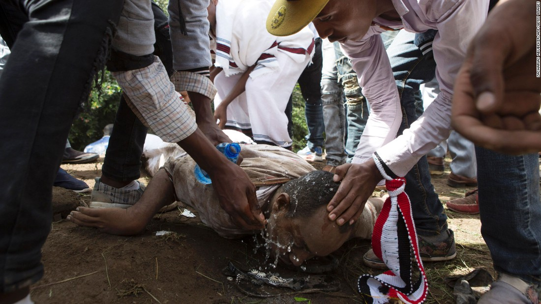 People help a man wash his eyes after police used teargas on festival participants.