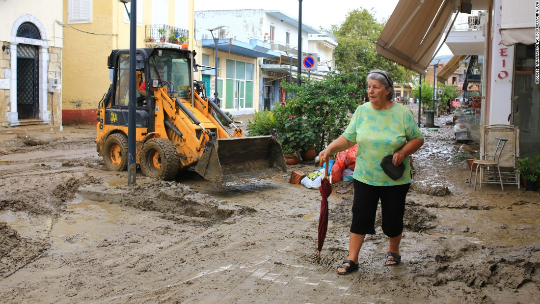 A woman walks on a mud-covered road as municipal employees try to clean an area in Kalamata, Greece, on Wednesday, September 7. Excessive rainfall in Kalamata damaged buildings and cars.