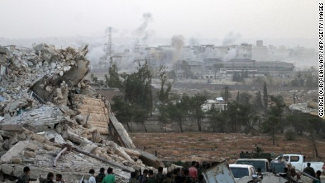 Syrian regime forces gather at the Kindi Hospital as smoke billows following aistrikes on Aleppo on October 2, 2016. Rebels had held the Kindi hospital since 2013, and capturing it allows government forces to threaten the opposition-held Heluk and Haydariyeh neighbourhoods. / AFP / GEORGE OURFALIAN        (Photo credit should read GEORGE OURFALIAN/AFP/Getty Images)