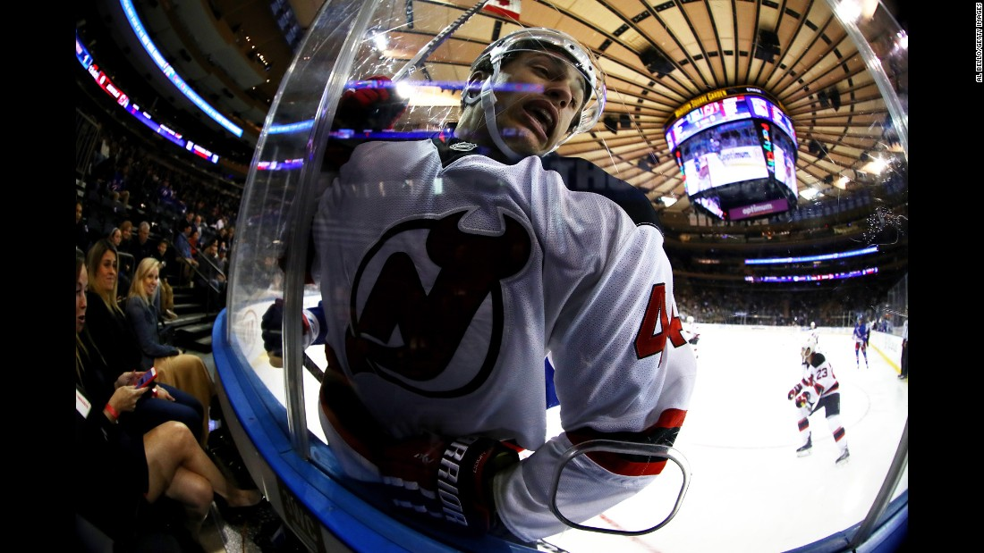 New Jersey's Miles Wood is checked into the boards during an NHL preseason game in New York on Thursday, September 29.