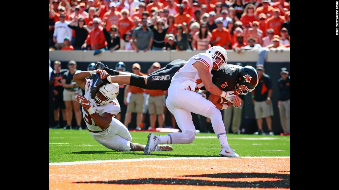 Oklahoma State quarterback Mason Rudolph is hit by two Texas players as he dives for the end zone on Saturday, October 1. Rudolph also passed for three touchdowns as Oklahoma State won 49-31 in Stillwater, Oklahoma.