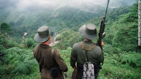 "FLORENCIA, COLOMBIA:  Two armed soldiers belonging to the Revolutionry Armed Forces of Colombia (FARC) monitor the Berlin pass, 07 March, near Florencia, in the  southern Caqueta province of Colombia, where cars are prevented from going through after the rebels decreed 06 March a ban on ""travel on roads and waterways for six days"". The rebels try to dissuade voters from casting their ballots in the 08 March elections for congress. According to the rebels, the elections 08 March are illegitimate because the left has been forced out of national politics, following the murder over the past years of thousands of Colombia's left-wing politicians and supporters. AFP PHOTO PEDRO UGARTE (Photo credit should read PEDRO UGARTE/AFP/Getty Images)"