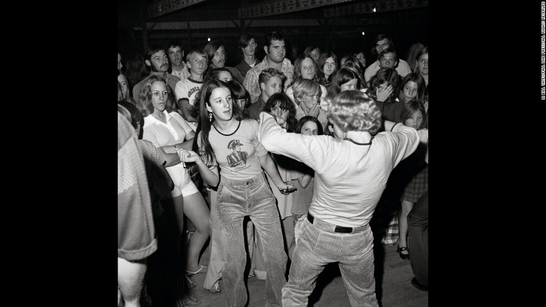 Many of Yates' photos suggest a story. Take this one, for example: While a couple dances in the foreground, the young woman in white glares disapprovingly.