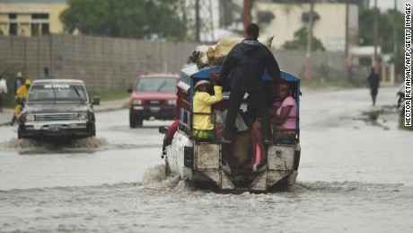 "A tap tap (public transportation) crosses the water left by the rain after hurricane Matthew, in Port-au-Prince, on October 4, 2016.  Hurricane Matthew made landfall in southwestern Haiti early Tuesday, crashing ashore as a powerful Category Four storm, US weather forecasters said. The National Hurricane Center said Matthew made landfall as an ""extremely dangerous"" storm near the village of Les Anglais at around 7 am (1100 GMT) with maximum sustained winds of around 145 miles (230 kilometers) per hour.  / AFP / HECTOR RETAMAL        (Photo credit should read HECTOR RETAMAL/AFP/Getty Images)"