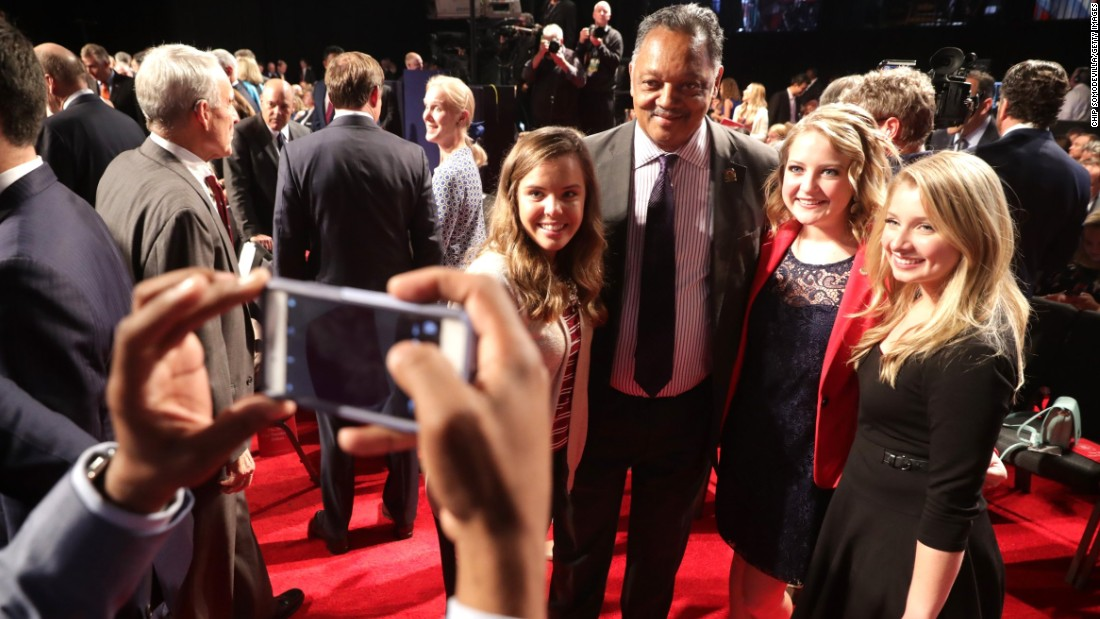 The Rev. Jesse Jackson takes photos with debate attendees prior to the debate.