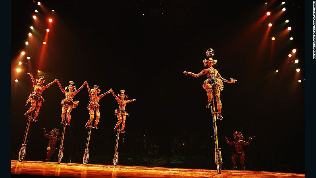 These Totem cast members balance on unicycles while juggling metal bowls, sometimes tossing them over their shoulders with their feet and catching them on their heads -- all without using their hands.