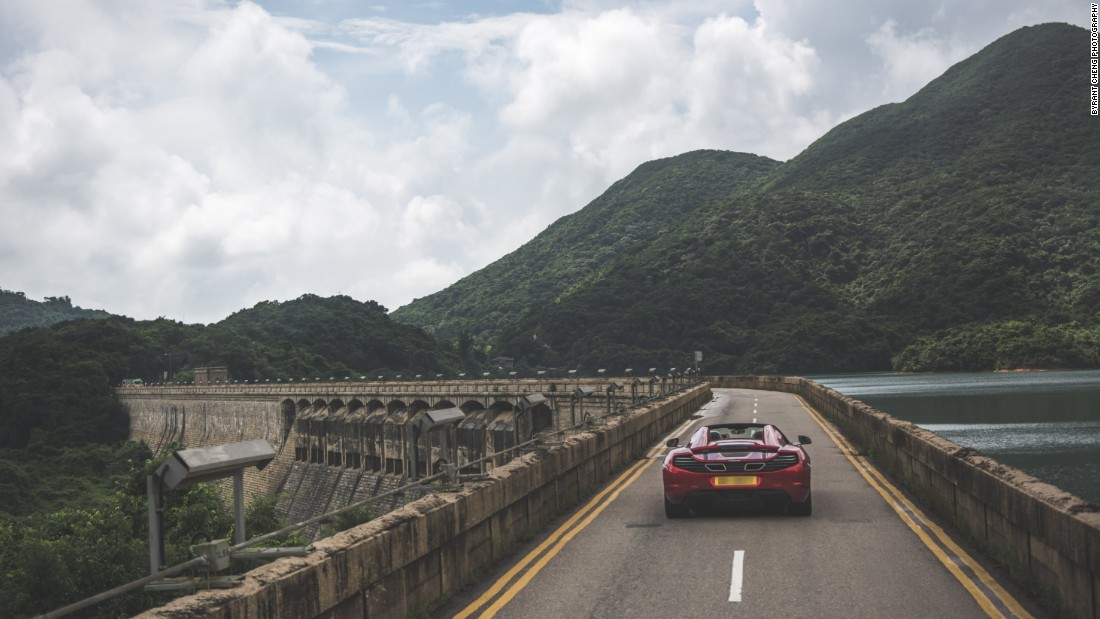 A narrow road crosses Tai Tam Tuk dam, which leads into Shek O Road's lush hills and beautiful coastal views.