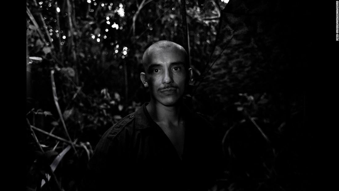 Danilo, a FARC rebel, is illuminated by a small flashlight. From 6 p.m. until 5 a.m., lighting was not allowed at the camp.
