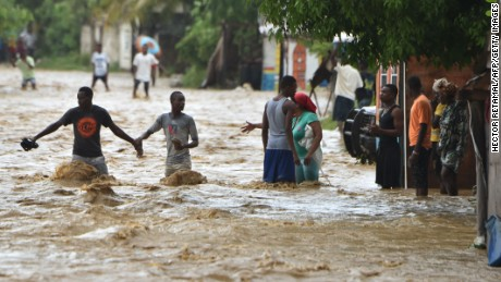 People try to cross the overflowing La Rouyonne river in the commune of Leogane, south of Port-au-Prince, October 5, 2016.