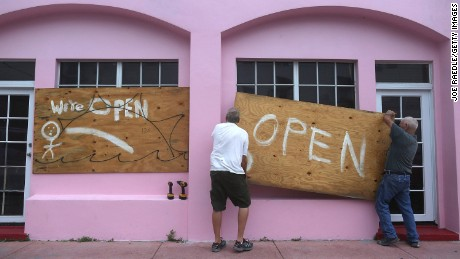 Kevin Forde and John Haughey put up plywood on a window as they prepare for Hurricane Matthew as it approaches the area on October 6 in Miami Beach, Florida.