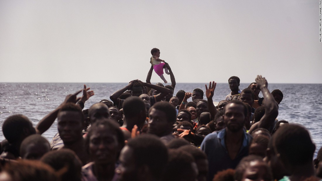 A child is lifted above the crowded boat as migrants wait to be rescued.