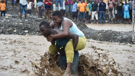 A man carries a woman across a  river where a bridge collapsed near Port-au-Prince. Hurricane Matthew has killed at least 108 people in Haiti.