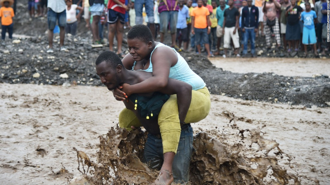 A man carries a woman across a river at Petit Goave on October 5. A bridge collapsed because of the storm.