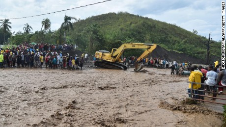 Haitians wait to cross the river n Petit Goave where a bridge collapsed cutting off a main route to the devastated south of the country