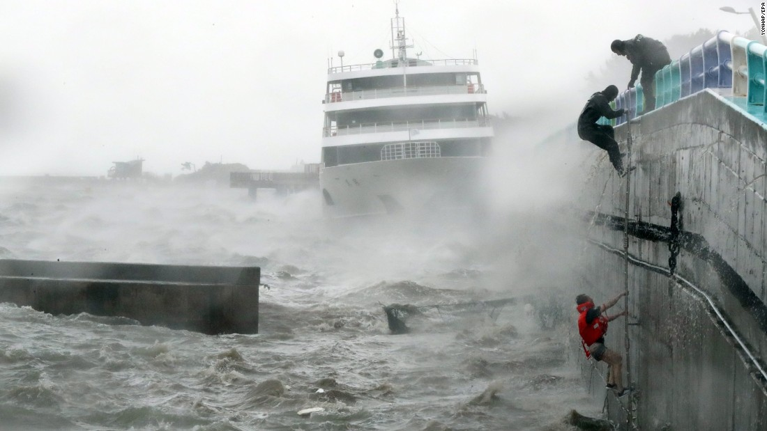 Crew members are rescued from their boat in Yeosu, South Korea, after Typhoon Chaba stranded them on Wednesday, October 5.