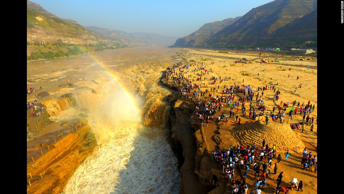 Tourists visit the Hukou Waterfall in Yan'an, China, on Sunday, October 2.