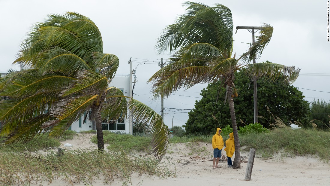 People stand on a beach in Broward County, Florida, as the storm approached the coast on Thursday, October 6.