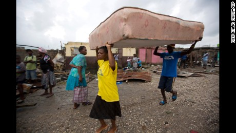 Residents take a mattress to a shelter after homes were destroyed in Les Cayes, Haiti.